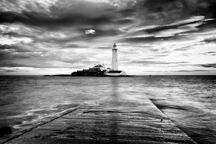 Black and white coastal view across the water looking towards a lighthouse, shot with a long exposure