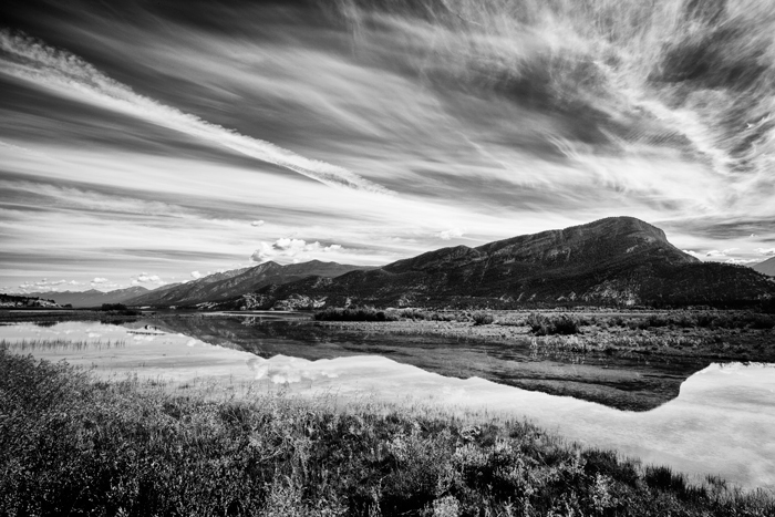 A black and white photo of a cloud streaked sky reflected in water with hill in background