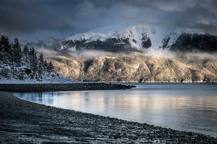 Coastal photography: rocky coastline with snow-capped mountain in background