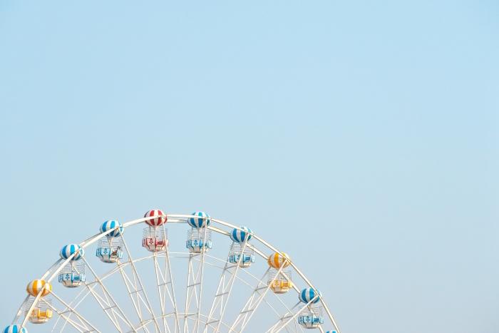 O topo de uma roda gigante contra um céu azul