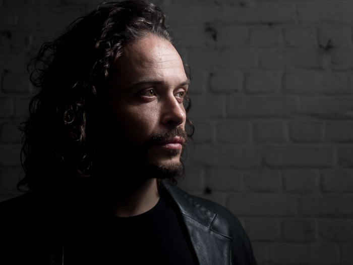 Low key portrait of a male model illustrating loop lighting with light modified by umbrella