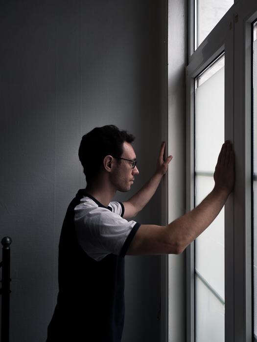 a portrait of a man gazing out a window, lit with subtle split lighting