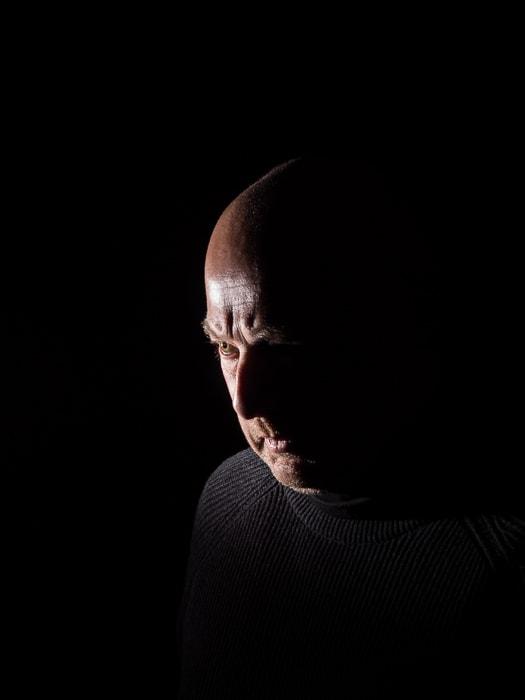 Low key portrait of a male model illustrating short lighting