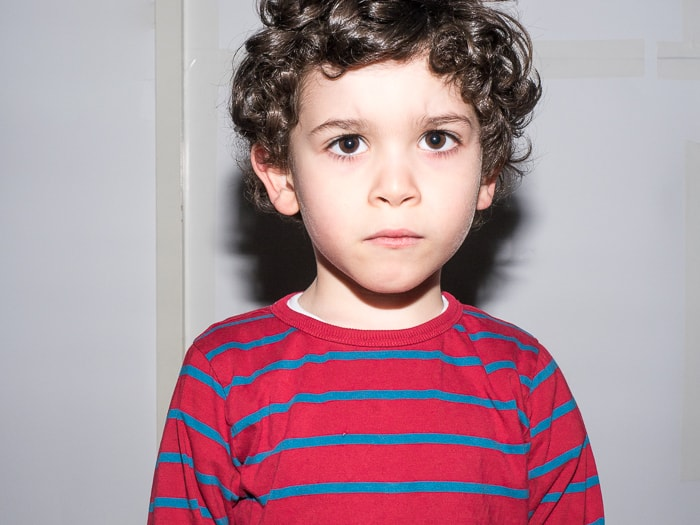 Portrait of young boy lit with hard light from direct flash