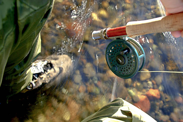 Artistic photo of a person fishing, showing the fishing rod and their boot