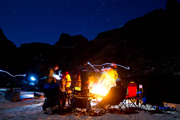 Photo of people around a campfire, showing camp life during outdoor photography
