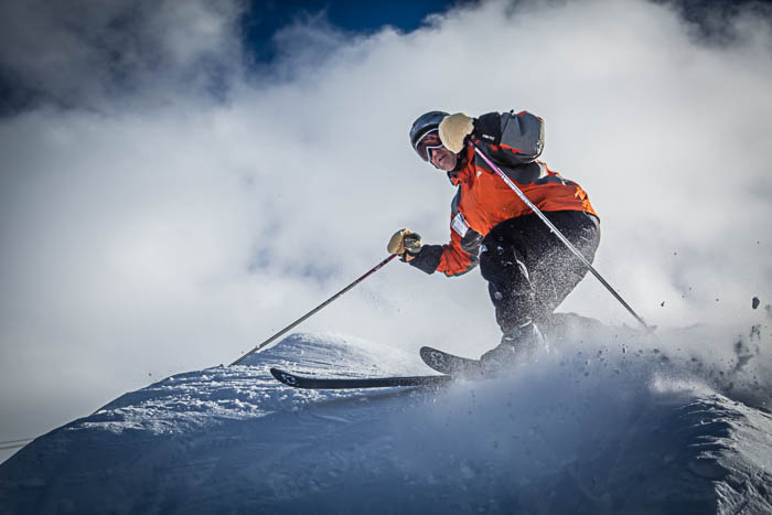 Picture of a skier turning, with powdered snow flying everywhere.