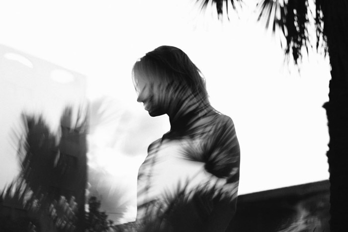a high contrast double-exposure silhouette of a woman and foliage