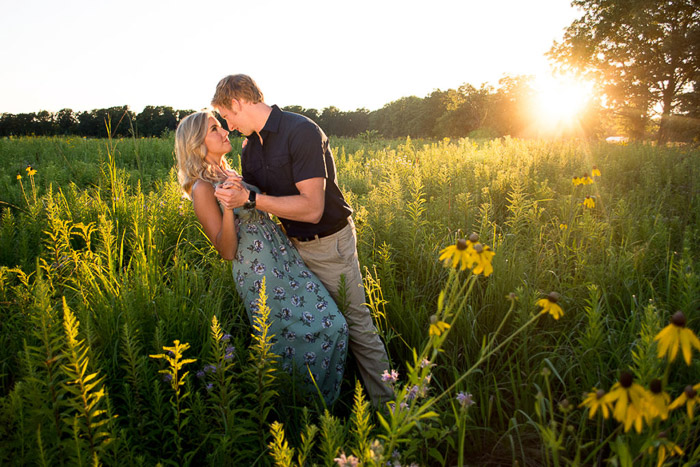 A man sweeps his girlfriend off her feet in a Golden Hour lit field in a calm countryside location