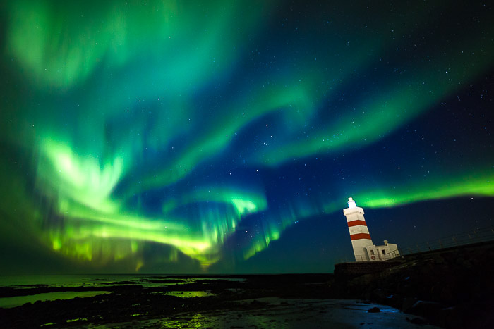 Northern lights picture with a lighthouse to the right, showing the Aurora Borealis colours