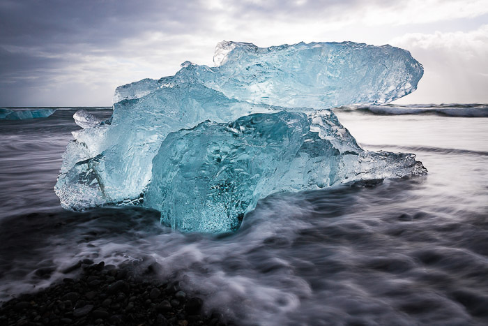 Natural ice sculpture in the shape of a large blue crystal, coming out of the waves