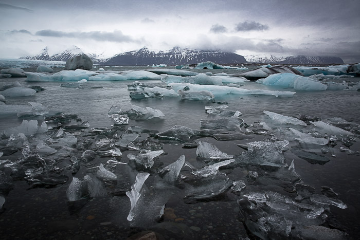 landscape picture of ice river with frozen pieces of ice floating in it and mountains in the distance, taken in Iceland
