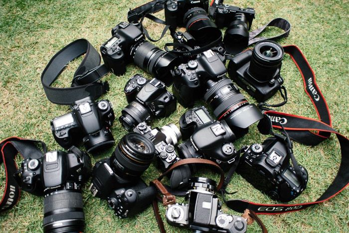 A pile of Canon cameras scattered on the grass.