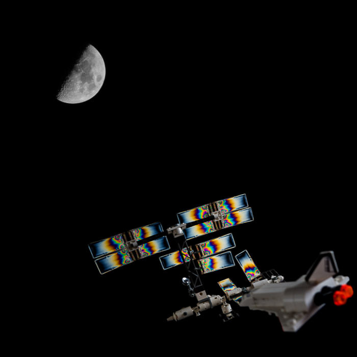 A Composite image of a photoelastic LEGO space station and the Moon