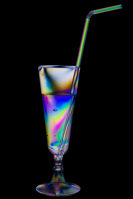 Rainbow effect on a plastic cocktail glass and drinking straw.