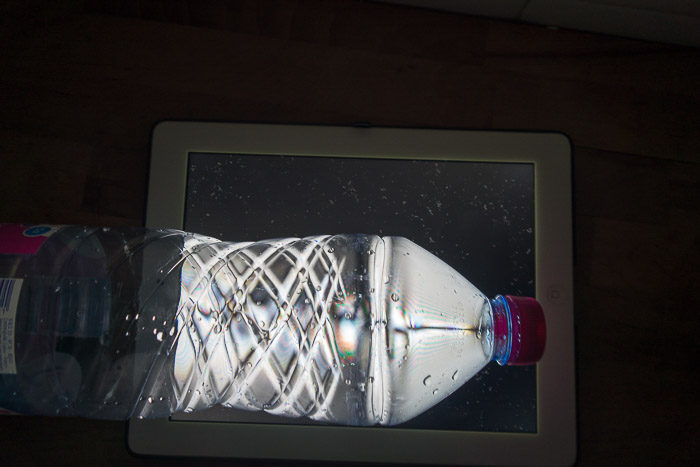 A PET drink bottles in front of a laptop screen