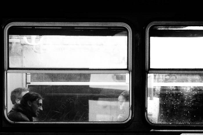 Two men inside a train compartment. Photo is black and white and photographed from the outside, looking in through the window.