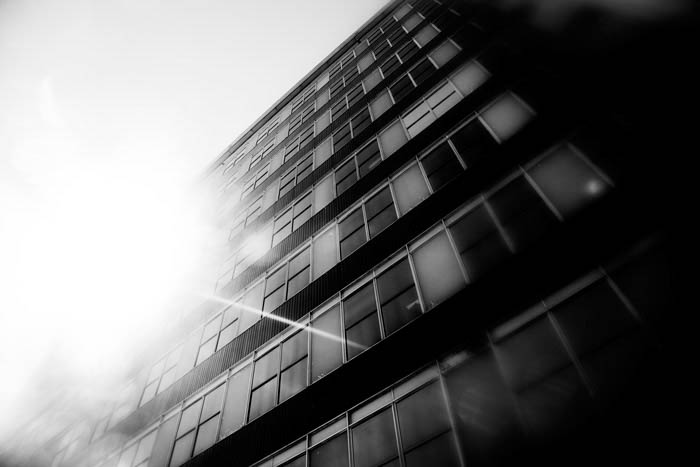 Black and white photo of a tall building, with sun reflection in windows. The photo is taken from street level, looking up.