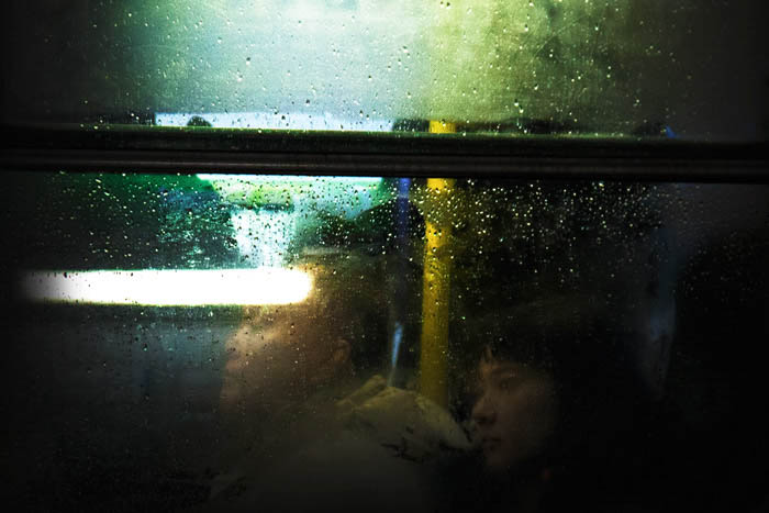 Look inside a train compartment. Photo is taken through the window, a man and a girl can be seen sitting inside.