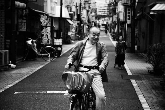 Urban Photography depicting a man on a bike, laughing. There is a woman in the background, to the right. The street is otherwise empty.
