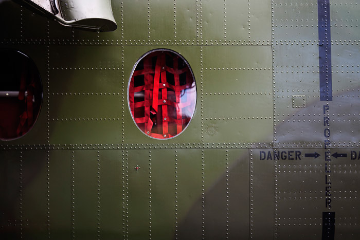 Cargo webbing visible through the window of a military plane.