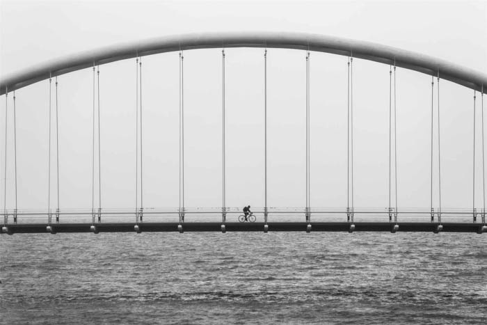 A photograph of a cyclist crossing a bridge for black and white photography