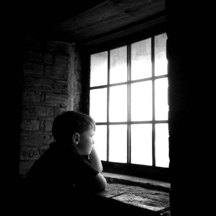 A boy looking out of the window, taken with a smart phone photography app