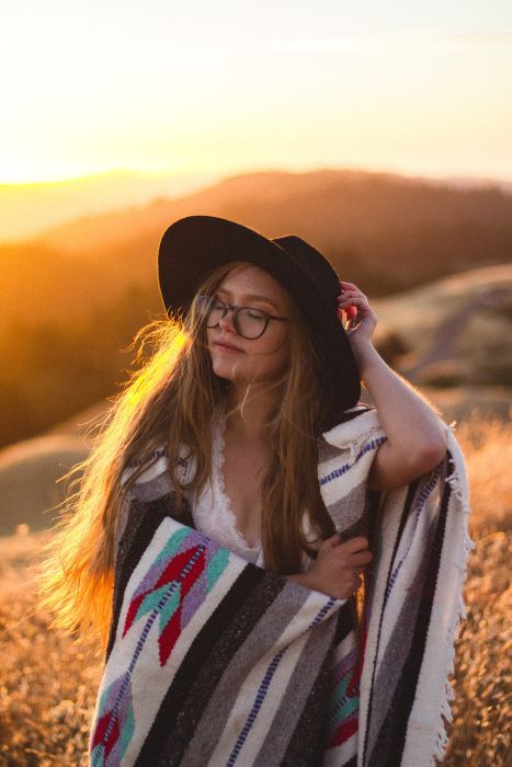 Girl in black wide rimmed hat and blanket in the sunset