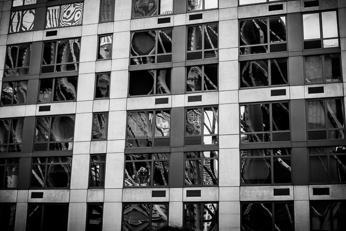 Distorted reflections in the windows of a high-rise building. Urban street photography. Monochrome reflections.