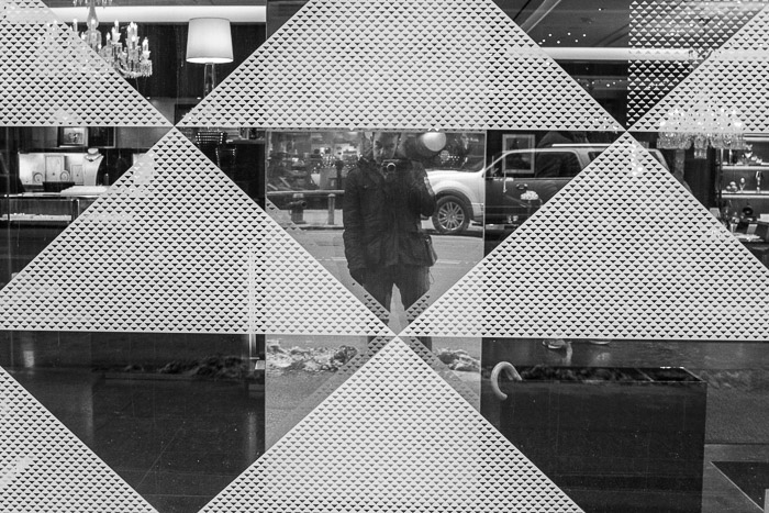 Self portrait taken against patterned window in black and white monochrome