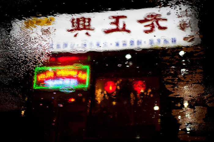 Chinese takeaway with neon signs reflected in the street puddles. Urban night photography