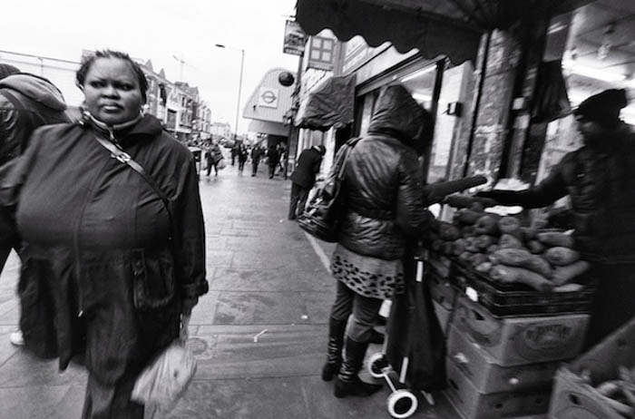 A street portrait of a woman walking down the street while others buy vegetables