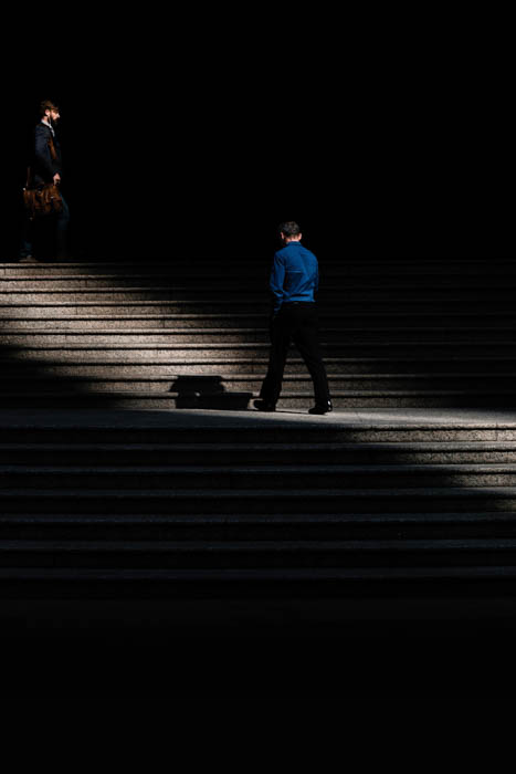 Two men walking within a slice of light