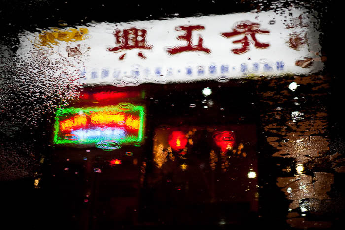 A reflection of a Chinese restaurant in a puddle on the street