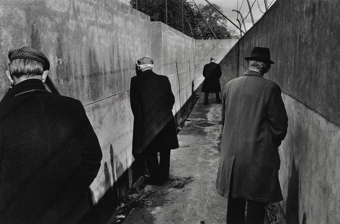 Black and white street photography of four men stand in a bleak corridor urinating