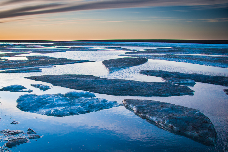 Sunset over a river covered with icecaps occasionally