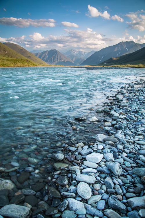 A river with rocks on its shore and mountains in the background