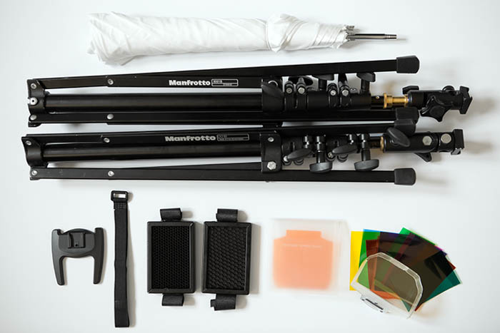assortment of photography accessories, including Manfrotto light stand and a flash gels filter kit