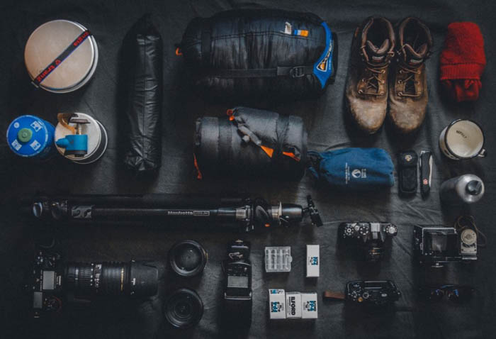 overhead shot of photography equipment including travel tripod, camera, lenses, flash and other accessories