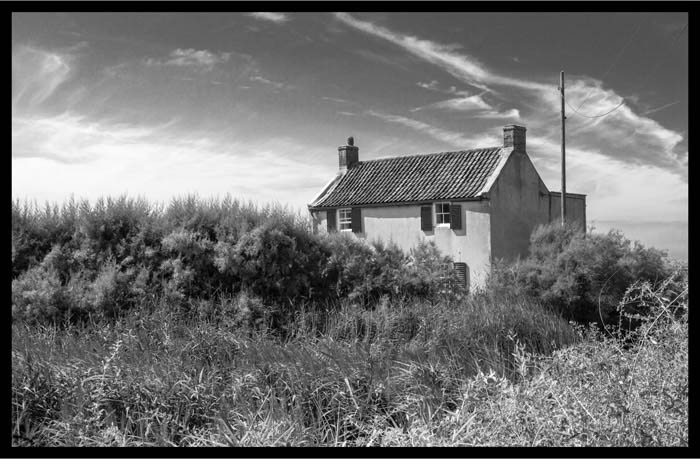 final image showing borders added in Lightroom to a black and white picture of a country house
