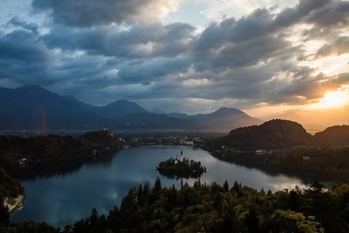 A picture of a sunset above the mountains and lake