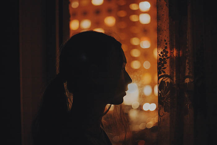 a silhouette self-portrait of a long haired girl in front of a windowsill