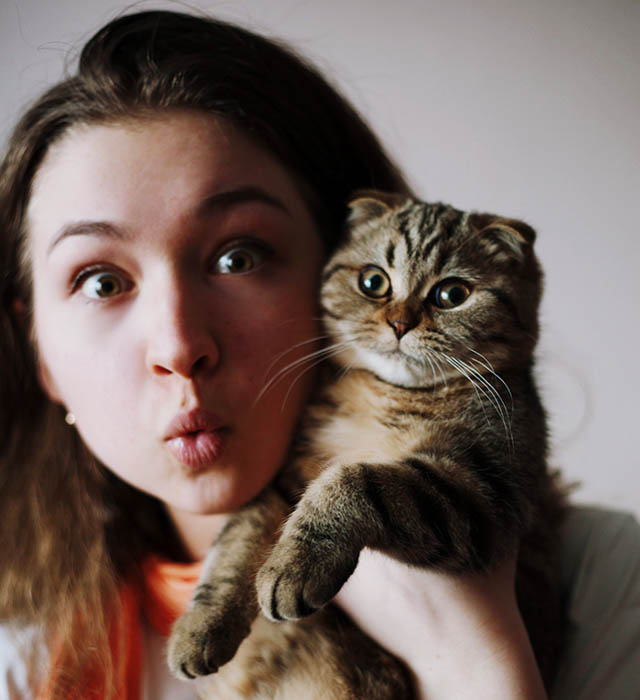 Cute self portrait photo of a girl and cat making silly faces.