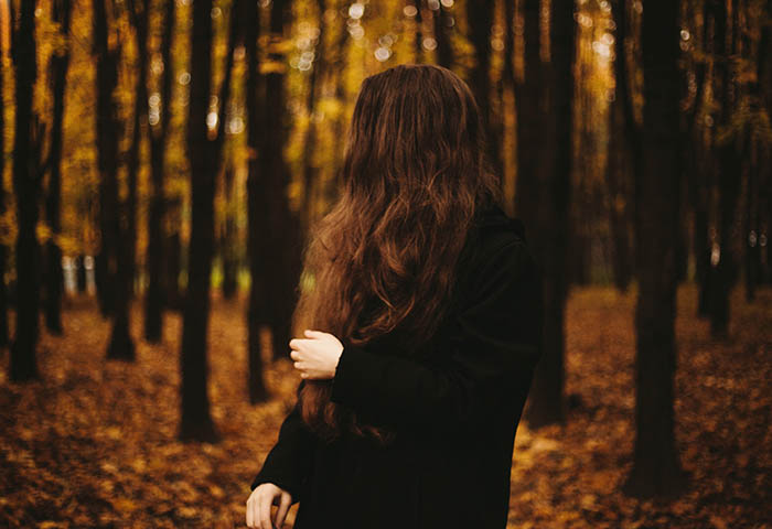 A woman dressed in black looking away from the photo, standing in a forest during autumn. Self portrait photography