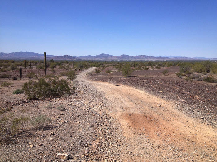 empty desert road in Arizona with mountains in the distance