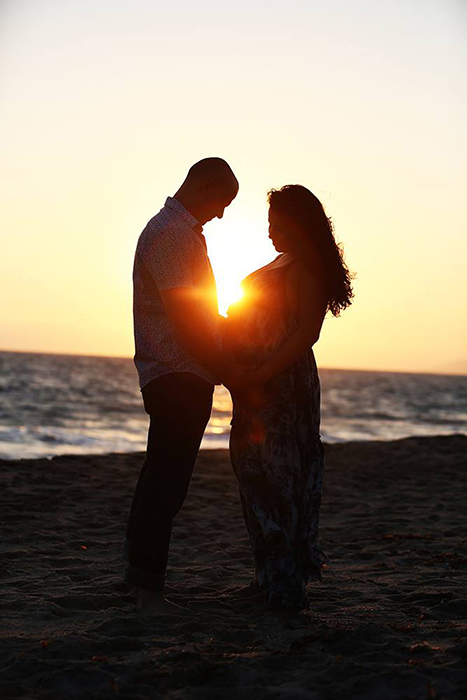photo of a couple on a beach with the sun setting in the background