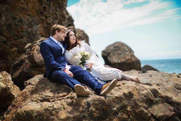 wedding photo of a couple lying on rocks near the sea