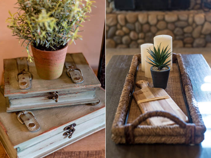 real estate photo of decor with a flowerpot on top of some books and a wooden tray with candles