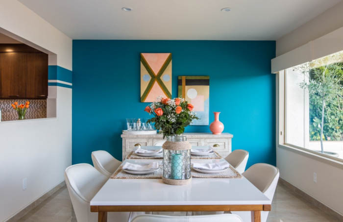 sunny dining room with white furniture and a blue wall in the background