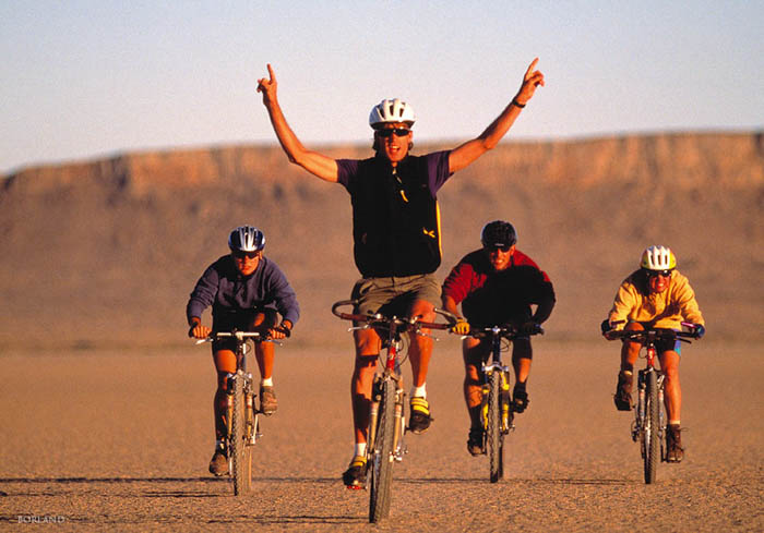 four men bicycling in a desert